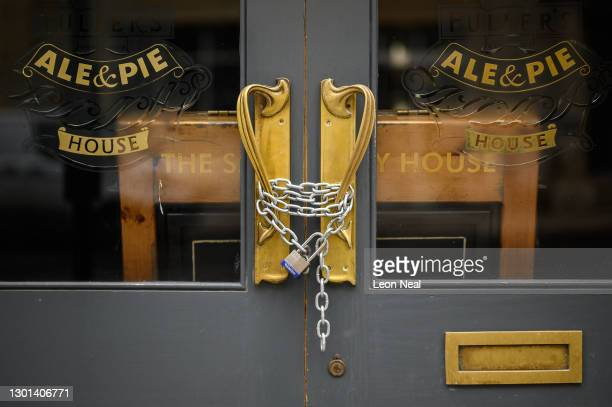 Padlock and chain secures the door of a temporarily-closed pub on February 10, 2021 in London, England. With a surge of COVID-19 cases fueled partly...