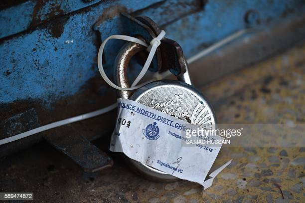 A padlock sealed by a member of the Indian Delhi Home Guard hangs from the door of a shop near the Red Fort area in New Delhi on August 14 ahead of...