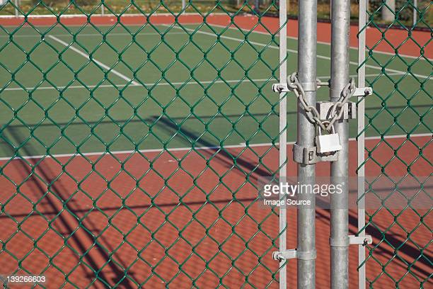 Padlocked chain-link security fence at a tennis court
