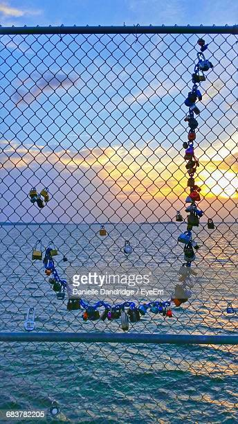padlocks on chainlink fence against lake murray during sunset - letra j - fotografias e filmes do acervo