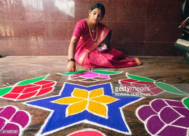 Padma gives finishes touches to a 'rangoli' a coloured powder decoration to celebrate the Diwali festival at her home in Bangalore 14 November 2001...