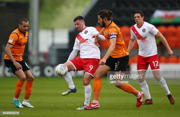 Padraig Amond of Newport County AFC and Dan Sweeney of Barnet FC compete for the ball during the Sky Bet League Two match between Barnet FC and...