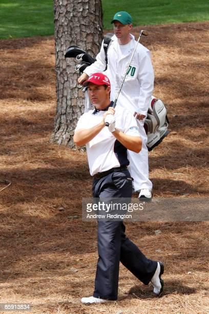 Padraig Harrington of Ireland plays his fourth shot from the pine needles as his caddie Ronan Flood looks on the second hole during the third round...