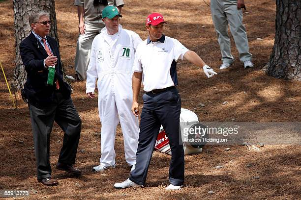 Padraig Harrington of Ireland seeks a ruling from the pine needles on the second hole as his caddie Ronan Flood looks on during the third round of...