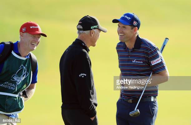 Padraig Harrington of Ireland shares a joke with his caddie Ronan Flood and coach Pete Cowen during practice for the Portugal Masters at Dom Pedro...