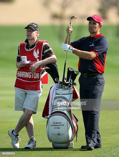 Padraig Harrington of Ireland waits with his caddie Ronan Flood on the eighth hole during the first round of The Abu Dhabi Golf Championship at Abu...