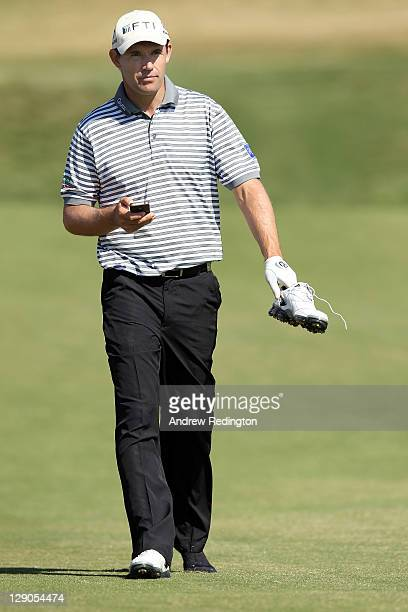 Padraig Harrington of Ireland walks along with one shoe off due to a bruised foot during the Pro Am prior to the start of the Portugal Masters at...