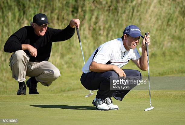 Padraig Harrington of the Republic of Ireland and Greg Norman of Australia line up putts on the 14th green during the final round of the 137th Open...