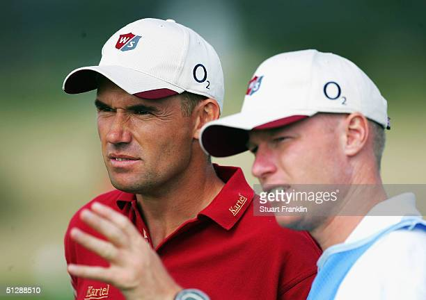 Padriag Harrington of Ireland and caddie Rownan Flood discuss his approach shot on the nineth hole during the third round of the Linde German Masters...