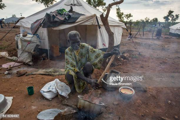 Pagarinya camp An elderly woman cooks outside her tent using firewood and a wooden stick to stir the food The Onward Struggle A refugee crisis in...