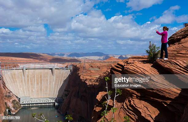 Page Arizona Glen Canyon Dam on Colorado River woman tourist taking IPhone pictures scenics with rocks and clouds for tourists West USA from above