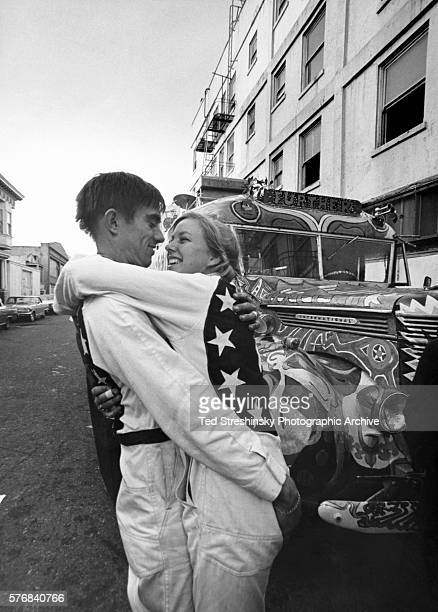 Page Browning and Doris Delay dressed in white coveralls decorated with stars from an American flag embrace The are part of the Merry Pranksters a...