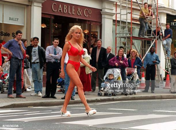 Page three model Melinda Messenger draws a crowd as she crosses the King's Road in London on the way to officially open the La Senza's lingerie store