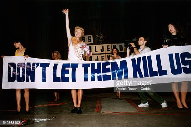 """Pageant winner Inela Nogic stands behind a banner as she waves to the audience during the 1993 Miss Sarajevo Pageant. The banner reads """"DON'T LET..."""