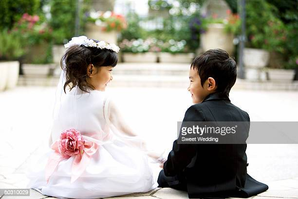 pageboy and flower girl sitting on staircase and holding hands, rear view - ring bearer stock pictures, royalty-free photos & images