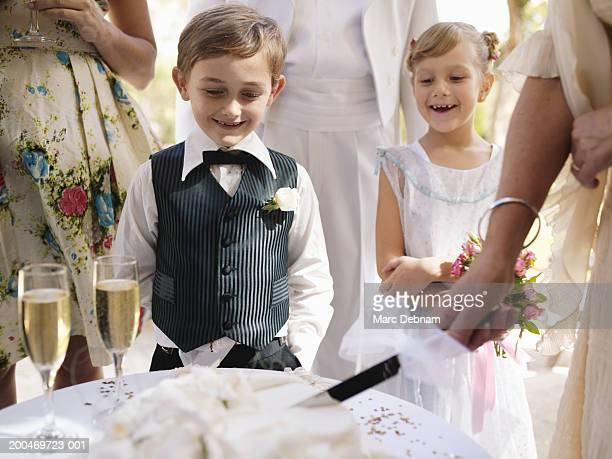 Pageboy and flowergirl (6-7)watching wedding cake being sliced