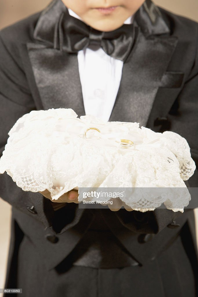 Pageboy holding rings, close-up : Stock Photo