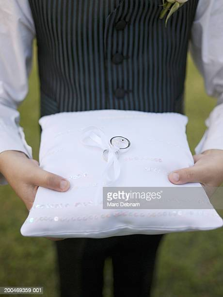 Pageboy (6-7) holding wedding ring, close-up