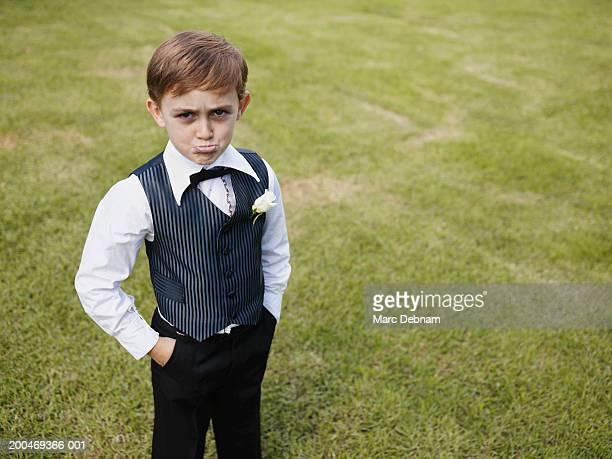 Pageboy (6-7) with hands in pockets, pulling face