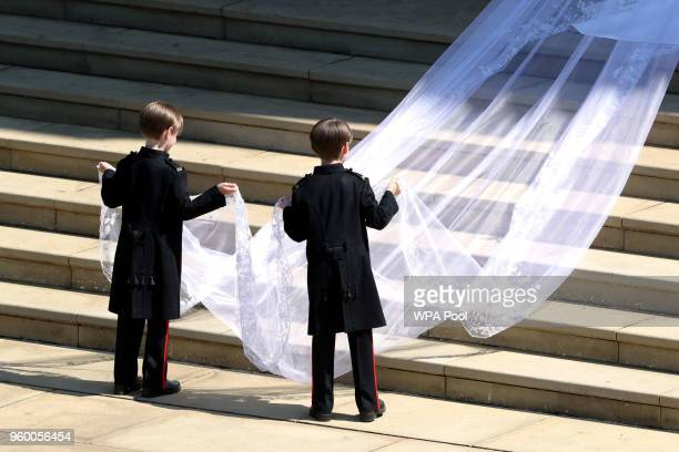 Pageboys hold the train of the dress of Meghan Markle as she arrives at St George's Chapel at Windsor Castle for her wedding to Prince Harry on May...