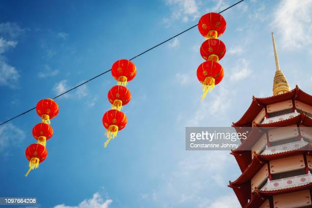 pagoda temple tower and red lanterns hanging against blue sky - pagode stock-fotos und bilder