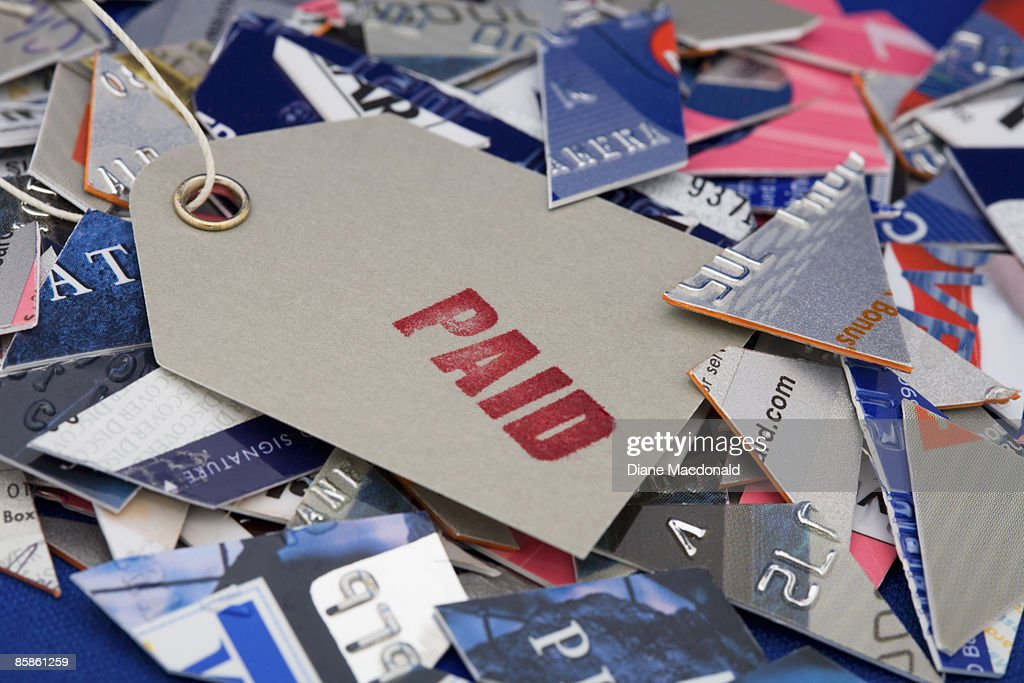 A paid label on top of cut up credit cards : Stock-Foto