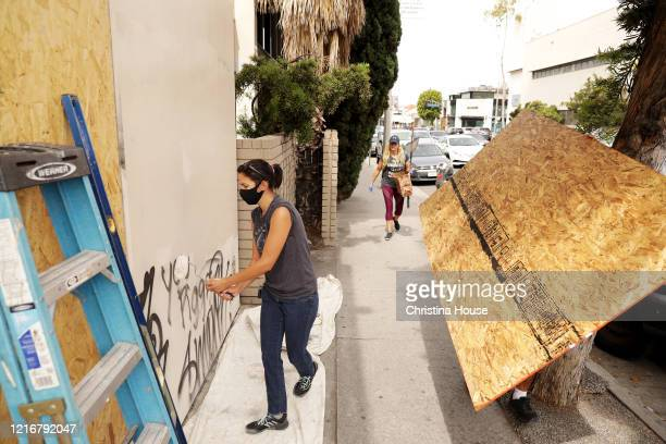 Paige Esquivel paints over graffiti at The Paper Bag Princess a shop on Melrose where she works on Sunday May 31 2020