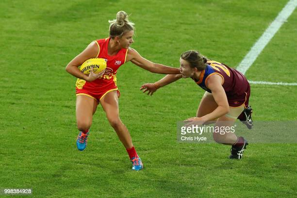 Paige Parker of the Suns is tackled during the AFLW Winter Series match between the Gold Coast Suns and the Brisbane Lions at Metricon Stadium on...