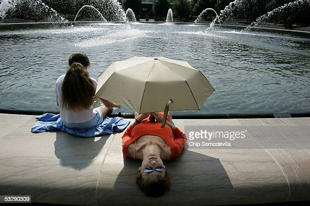 Paige Rose, 12 years-old, and her mother, Cindy Rose, of St. Louis, MO, take shade under an umbrella while they dip their feet in the fountain in the...