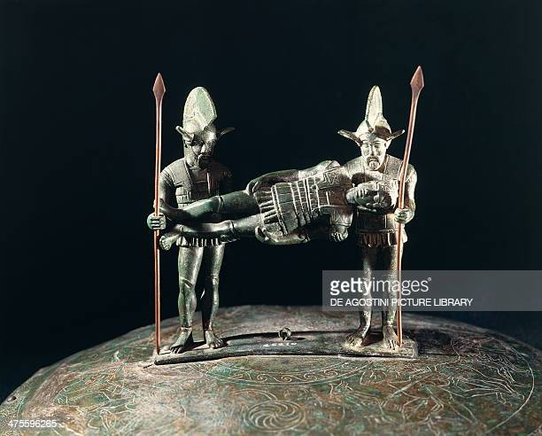 Pail handle with armed warriors holding up a wounded comrade bronze from the Colombella necropolis of Colombella Lazio Italy Etruscan civilisation...