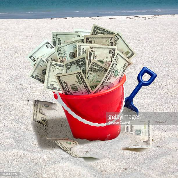 Pail of Money on beach