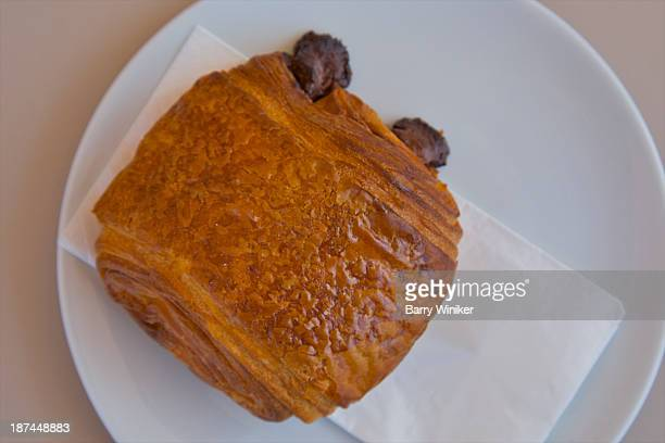 Pain au chocolate on napkin on top of white plate