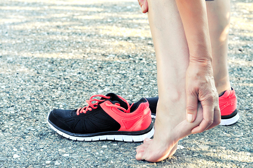 Pain in the foot.Running injury leg accident- sport woman runner hurting massaging painful sprained ankle in pain.Athlete woman has heel injury, sprained ankle during running training. 1071078080