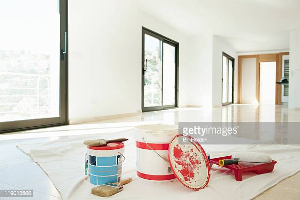 paint and brushes in empty living room - farbeimer stock-fotos und bilder
