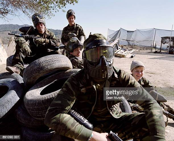 Paint ball battle, players in camouflage outfits resting on tires