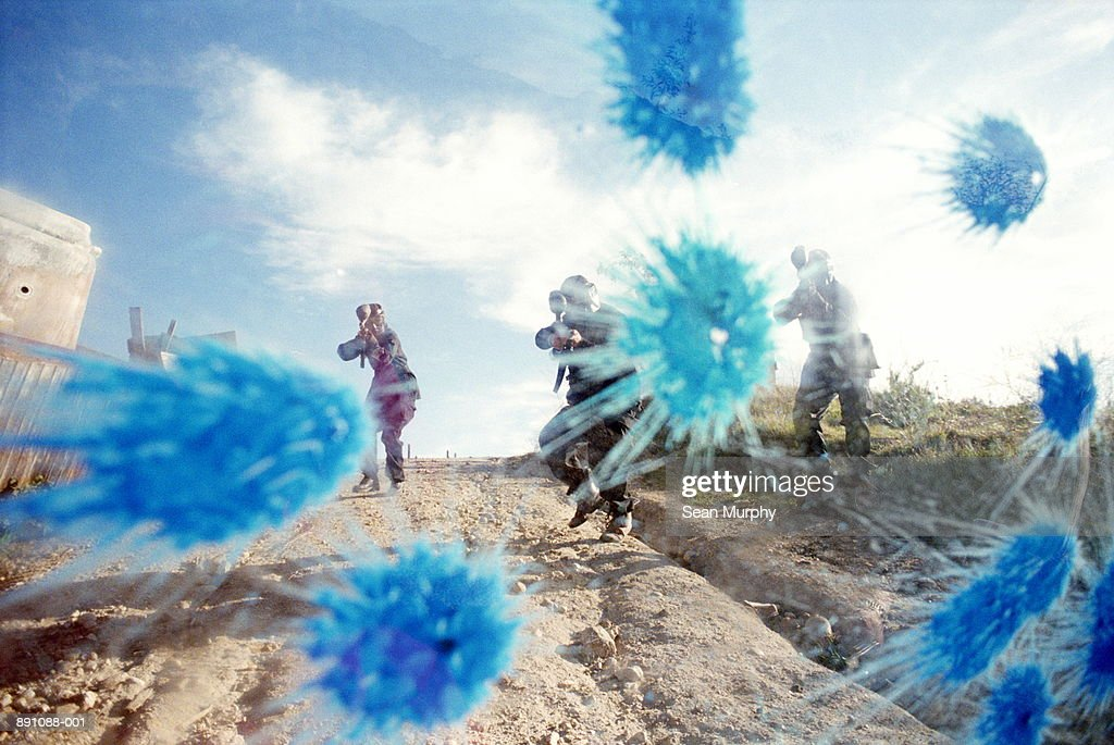 Paint ball battle, players in camouflage shooting paint on glass : Stock Photo
