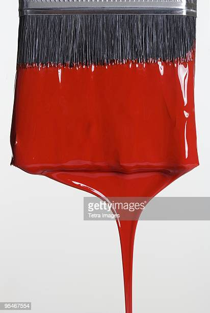 Paint brush dripping red paint
