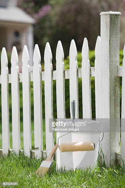 paint bucket next to white picket fence - whitewashed stock photos and pictures
