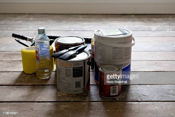 Paint cans and brushes in empty house