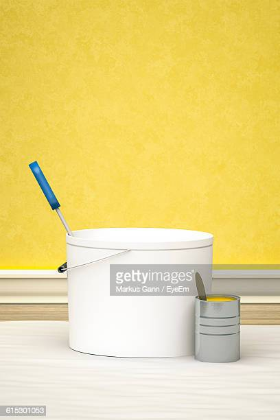 Paint Cans With Paintbrush Against Yellow Wall