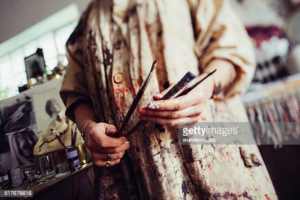 Paint covered hands of an artist in smock holding paitnbrushes
