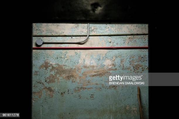 Paint falls from the wall along the route to a former Civil Defense fallout shelter beneath the OysterAdams School April 17 2018 in Washington DC In...