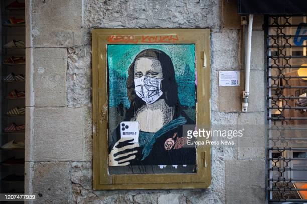 Paint of a Mona Lisa with a mobile phone and a mask work of the graffiti artist TV Boy called 'Mobile World Virus' in reference of the cancellation...