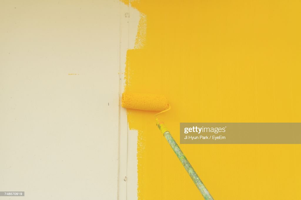 Paint Roller On Yellow Wall At Home : Stock-Foto