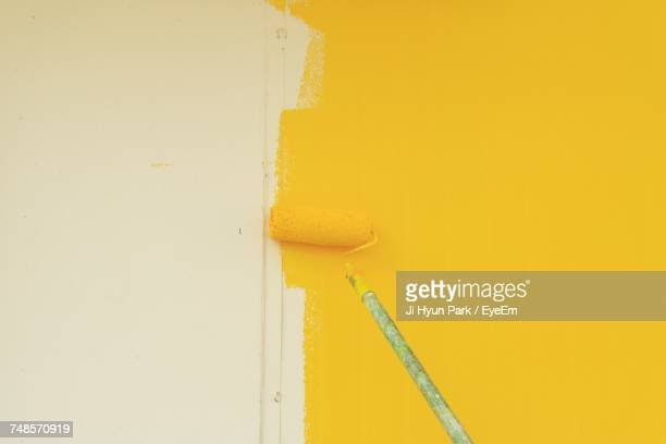 Paint Roller On Yellow Wall At Home