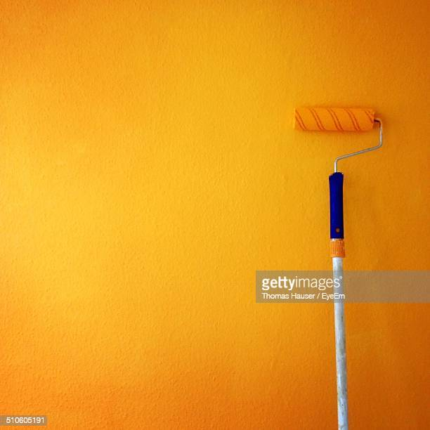 paint roller on yellow wall - paint roller stock pictures, royalty-free photos & images