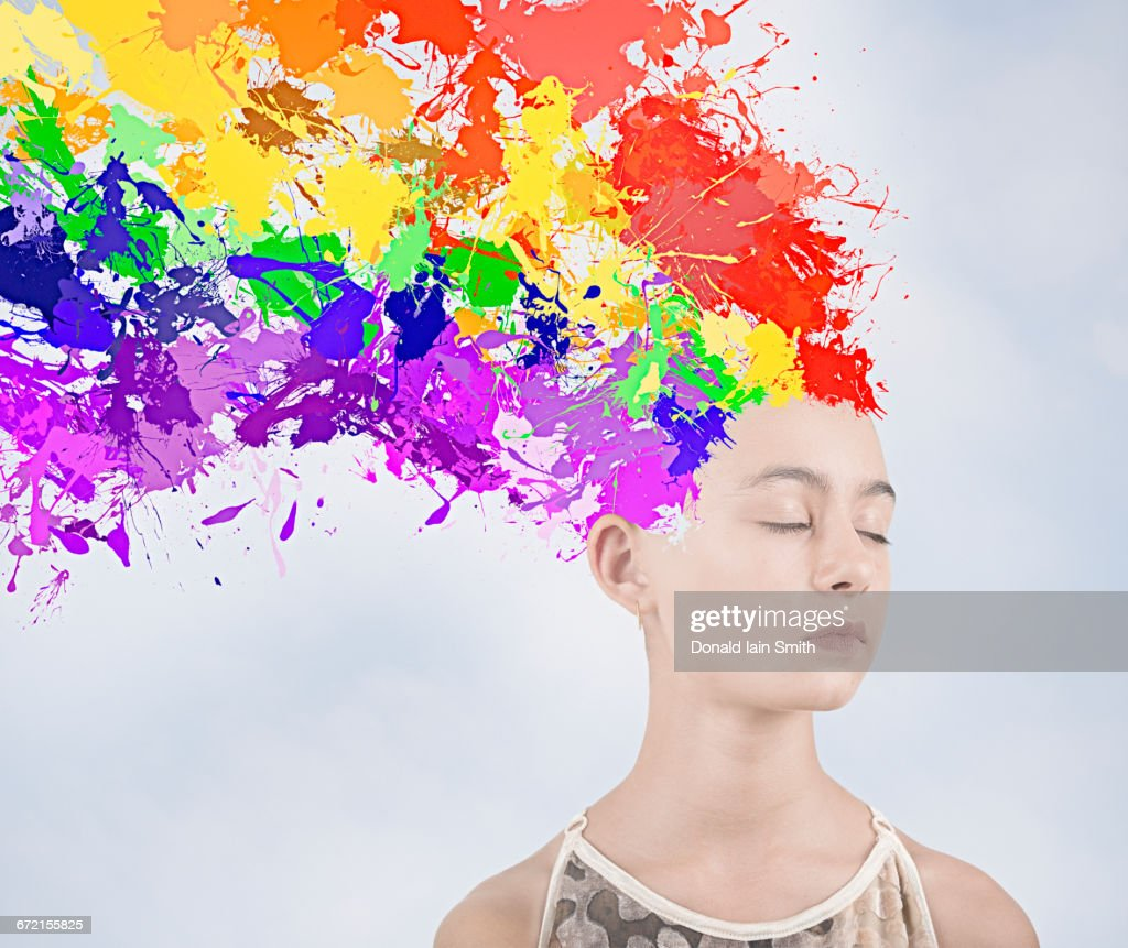 Paint splatter exploding from head of Mixed Race girl : Stock Photo