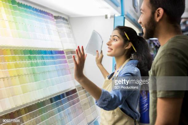 Paint store employee assists male customer