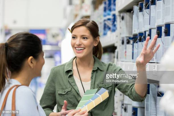 paint store salesperson helping female customer - saleswoman stock photos and pictures