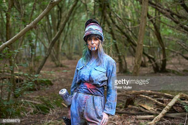 Paintball player in paintball wear marked with paint